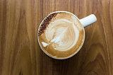 Leaf shaped coffee milk foam in white ceramic cup