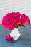 Mauve roses in vase on blue table
