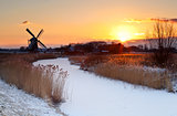 sunrise by windmill in winter
