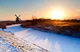 sunrise over Dutch windmill and frozen canal