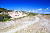 path in sand dunes over blue sky