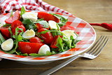 salad with fresh tomatoes, arugula and quail eggs