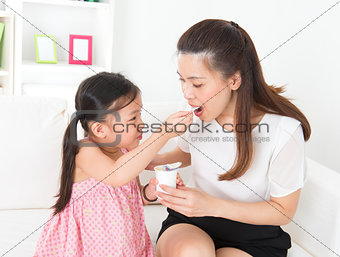 Beautiful child feeding mother yogurt