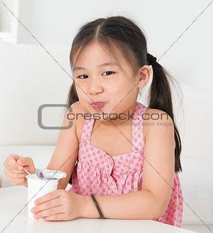 Asian kid eating yoghurt