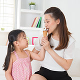 Kid feeding mum ice cream
