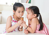 Asian kids eating ice cream cone