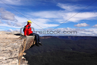 Sitting on Top of the World - hiker rests and admires views of B