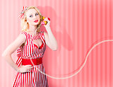 Retro housewife in 50s fashion on vintage phone
