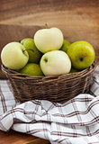Fresh apples in basket on wooden table