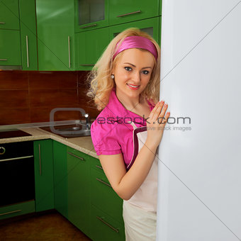Housewife in the kitchen with fridge