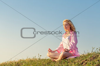 Blonde girl meditating in yoga pose
