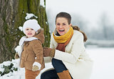 Happy mother and baby playing outdoors in winter