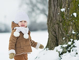 Happy baby playing outdoors in winter