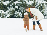 Happy mother and baby walking outdoors in winter