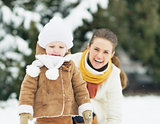Happy mother and baby playing in winter outdoors
