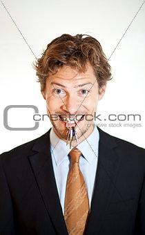 Smiling businessman holding keys between his teeth