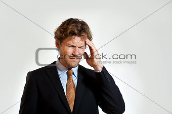 Aching businessman grabbing his head in pain