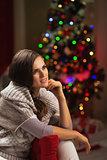 Portrait of thoughtful young woman near christmas tree