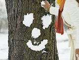 Young woman making face for tree using snow