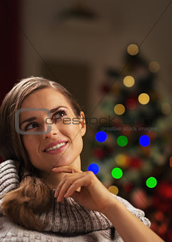 Portrait of thoughtful young woman near christmas tree looking o