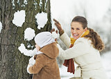 Happy mother and baby making face for tree using snow