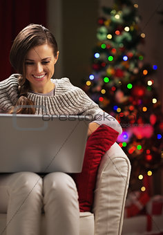 Smiling young woman near christmas tree using laptop
