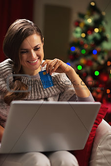 Smiling young woman with laptop and credit card near christmas t