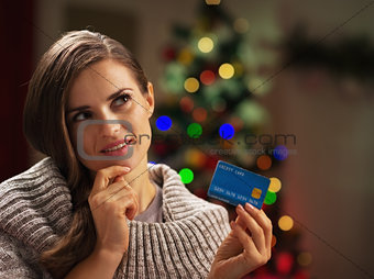 Portrait of thoughtful young woman with credit card near christm