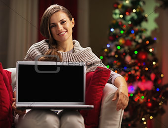 Smiling young woman showing laptop blank screen