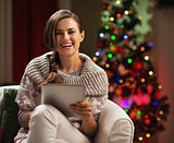 Smiling young woman near christmas tree using tablet pc