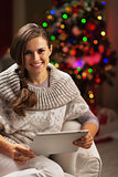 Happy young woman near christmas tree using tablet pc