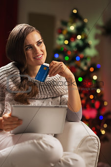 Thoughtful young woman with credit card and tablet pc near chris
