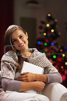 Happy young woman near christmas tree hugging tablet pc