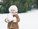 Baby playing with snow in winter park