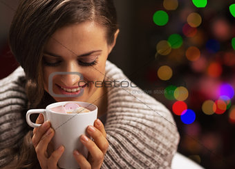 Happy woman with cup of hot chocolate with marshmallow in front