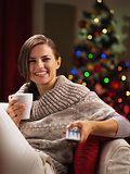 Happy young woman with cup of hot beverage near christmas tree w