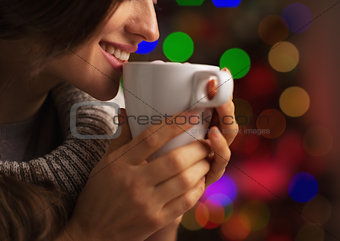Closeup on smiling young woman with cup of hot chocolate with ma
