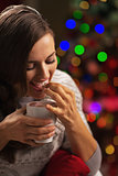 Happy young woman with cup of hot beverage eating marshmallow in