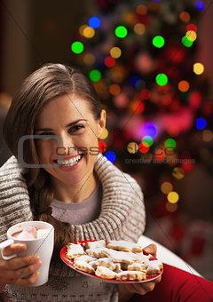 Portrait of smiling young woman with cup of hot beverage and chr
