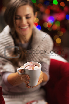 Closeup on cup of hot chocolate with marshmallow in hand of smil