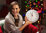Smiling young woman near christmas tree showing clock