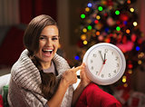 Smiling young woman near christmas tree pointing on clock