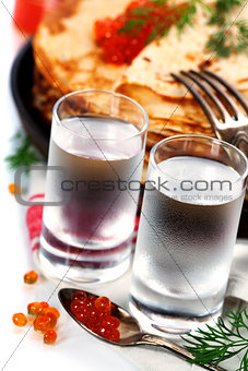 Russian vodka with pancakes and red caviar