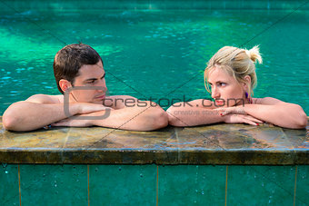 Sad and unhappy couple in swimming pool