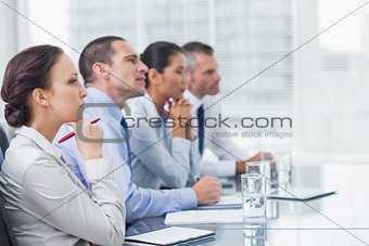Thoughtful coworkers listening to presentation