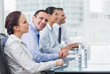 Businessman smiling at camera while his colleagues listening to presentation