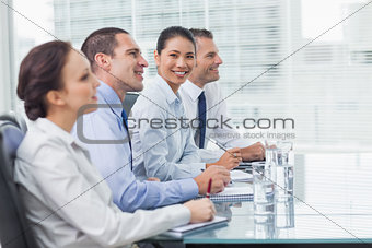 Businesswoman smiling at camera while her colleagues listening