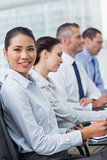 Cheerful employee attending presentation with her colleagues