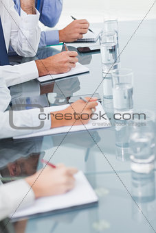 Close up on workmates taking notes while attending presentation