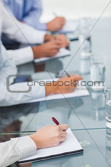 Close up on workmates taking notes during presentation